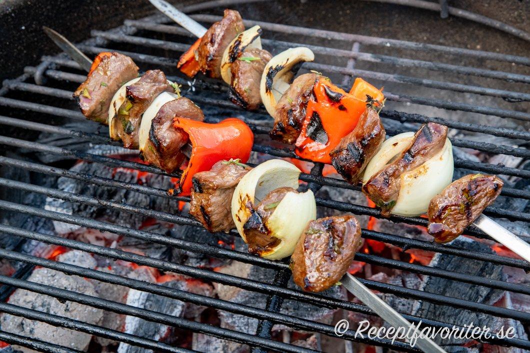 Grillspett med kött, lök och paprika på grillen