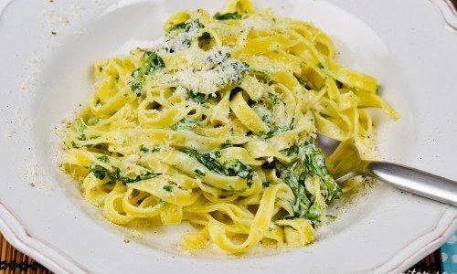 Pasta som tagliatelle med spenat, mascarpone och parmesan i tallrik