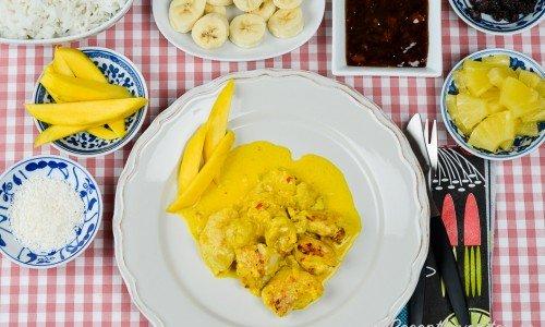 Servera kycklingen med kokos, färsk mango, kokt ris, banan, mango chutney, russin och ananas.