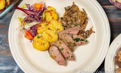 Älgfilé med trattkantarellsås och minihasselbackspotatis samt sallad på tallrik.