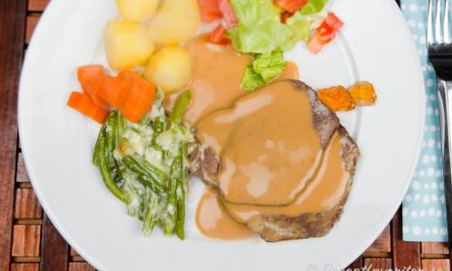 Älgstek med gräddsås på skyn, gratinerad gröna bönor, kokt potatis, morot och sallad samt gele.