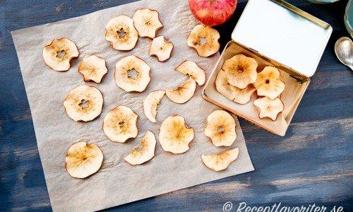 Äppelchips på bakplåtspapper och i burk