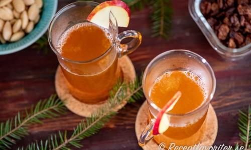 Två glas varm äppeldrink med must, sprit som bourbon, citron och kanel garnerad med en skiva äpple.