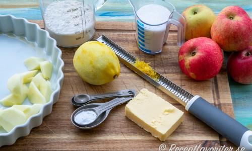 Ingredienser till pajen - äpplen, vetemjöl, citron, bakpulver, socker och smör.