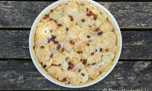 Det förgräddade pajskalet fylls med tunt skivade äpplen som blandats med socker, russin och kokos.