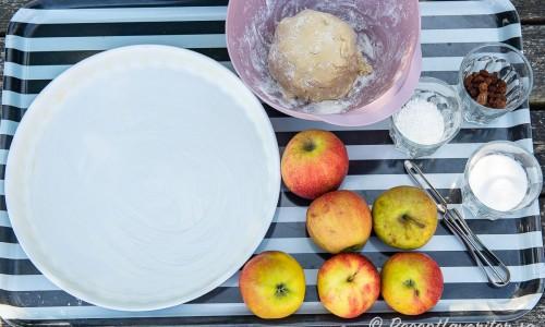 Till tarten behöver du bland annat en smord pajform, pajdeg, äpplen, socker, kokos och russin.