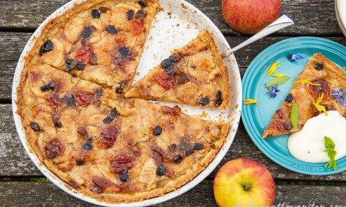 Äppeltarte i pajform serverad på tallrik i bit med vaniljsås.