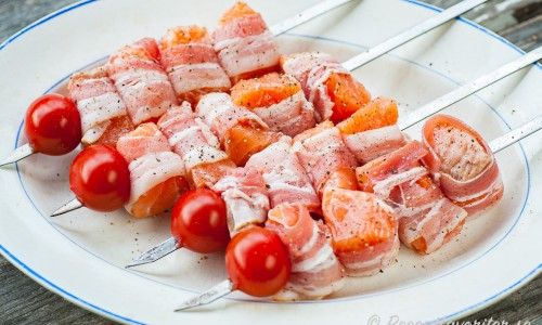 Baconlindad lax på spett med tomat redo för grillen.