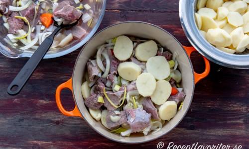 Köttet varvas med potatis i grytan