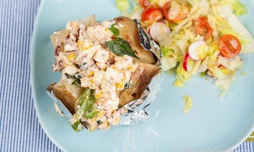 Bakad potatis med fetaoströra och sallad.