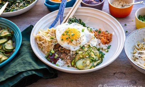 En tallrik Bibimbap - koreansk rispytt med kött, stekt ägg, chilipicklad gurka, sesammarinerade böngroddar och spenat; kimchi, rostade sesamfrön, salladslök samt gochujang koreansk chilisås.
