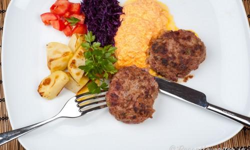 Biff a la Lindström kan serveras med valfria tillbehör - här med rostad potatis, tärnade tomater, riven rödkål och en tzatziki med riven morot.