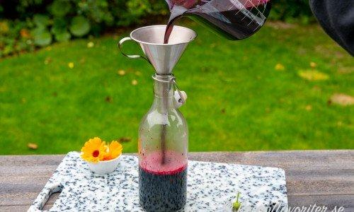 Blåbärssaften hälls upp i ren flaska