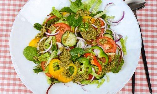 Blandad sallad med paprika, tomat, rödlök och gurka med pestodressing.