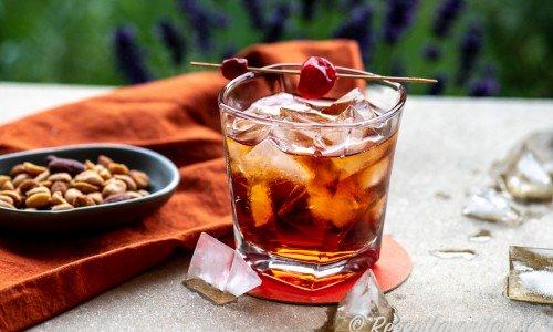 Boulevardier cocktail i glas med is och nötter