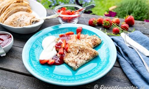 Bovetepannkakor serverad på tallrik med jordgubbssylt, jordgubbar och vispad grädde.