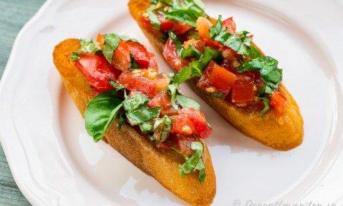 Bruschetta - grillade bröd toppade med vitlök, mogna tomater, avokado, olivolja och färsk basilika.