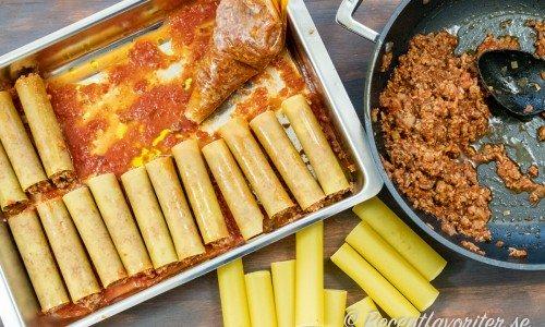 Pastarören fylls med köttfärsröran på ett lager tomatsås i formen.