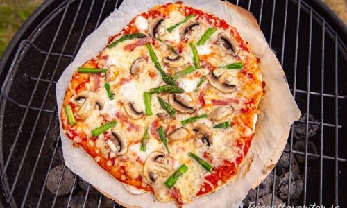 En capricciosa som gräddas på pizzasten med bakplåtspapper i grillen under lock.