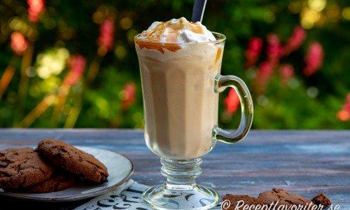 Caramel Frappuccino i glasmugg med grädde och kolasås samt sked.
