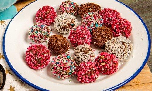 Chokladbollar i olika varianter med kokosflingor, pärlsocker eller strössel på tallrik.