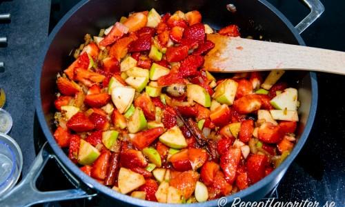 Jordgubbar, äpple, chili med flera ingredienser kokas i panna till chutney