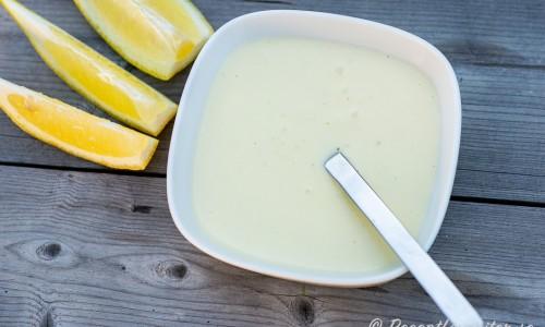 Varm citronsås serverad i skål med citronklyftor bredvid