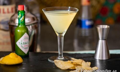Cocktail med grön tabasco, tequila, vit chokladlikör, Lillet blanc och citron i martiniglas.