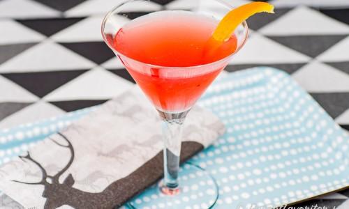 Cosmopolitan cocktail i Martiniglas med en strimla apelsin.
