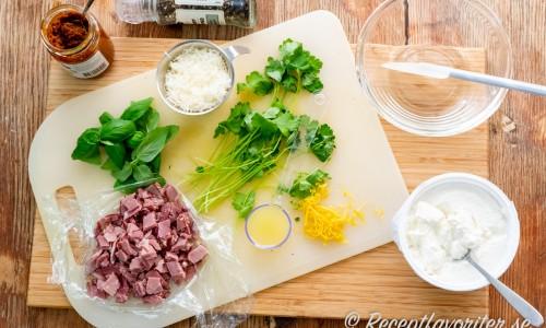 Ingredienser att toppa bröden med: röd pesto, svartpeppar, färsk basilika, rökt tärnad vildsvinsstek, riven parmesan, riven citron, färskpressad citron, bladpersilja och ricotta.