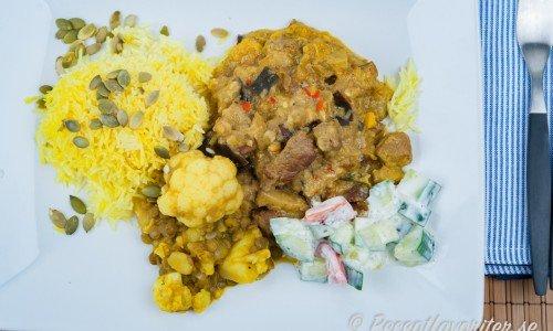 Currygryta med biff serverad på tallrik med tillbehör