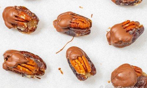 Dadlar med pekannötter doppade i choklad på bakplåtspapper