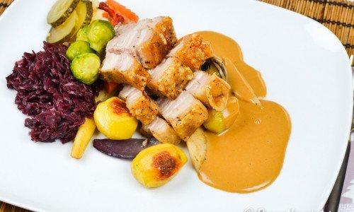 Dansk fläskstek serverad med rostad potatis och rotfrukter, gräddig skysås, rödkål, inlagd gurka och pickles.