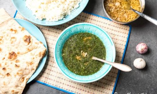 Egyptisk grönsaksgryta eller tjock soppa Molokhia eller Mulukhiyah serverad med arabiskt bröd, ris och lök, vitlök och chili fräst i olja.