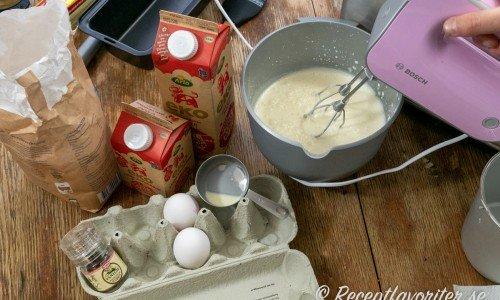Ingredienser till vaniljglassen - vaniljstång i kvarn, socker, mjölk, grädde och ägg.