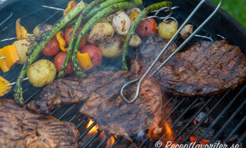 Entrecote grillas på utegrill med grönsaker.