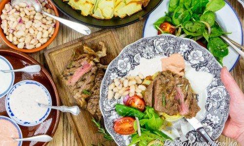 På bilden är den ugnsrostade potatisen serverad till kött (grillad entrecote) samt en spenat- och tomatsallad, marinerade vita bönor samt tre kalla såser.