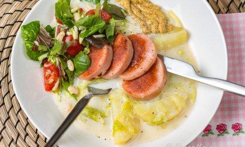 Falukorv med stuvad kål och potatis på tallrik med tillbehör
