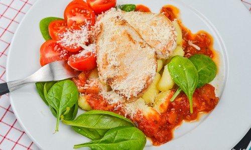 Gnocchi med stekt kycklingfilé och tomatsås samt parmesan på tallrik