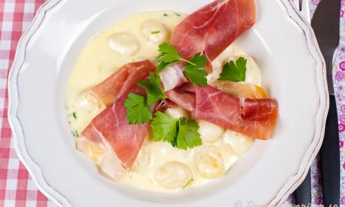 Färsk pasta eller Gnocchi med grädde, parmaskinka och tryffelolja på tallrik
