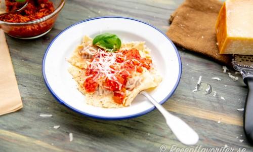 Färsk ravioli fylld med köttfärsfyllning och serverad med tomatsås och parmesan på tallrik