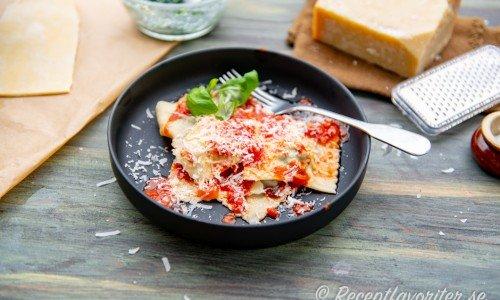 Färsk ravioli fylld med ricotta och spenat på tallrik.