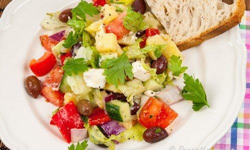 Fetaostsallad med kokt potatis, paprika och oliver i god dressing på tallrik.