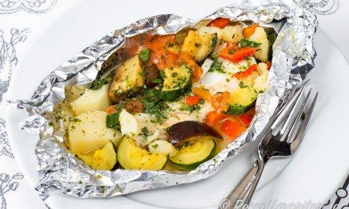 Fisk i folie med grönsaker och potatis på tallrik