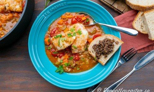 Fiskgryta med lubb på italienskt vis på tallrik med surdegsbröd och tapenade