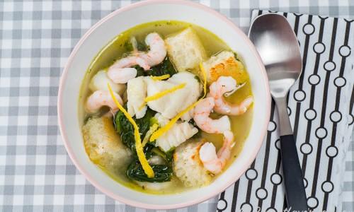 Klar fisksoppa med torsk och räkor i soppskål