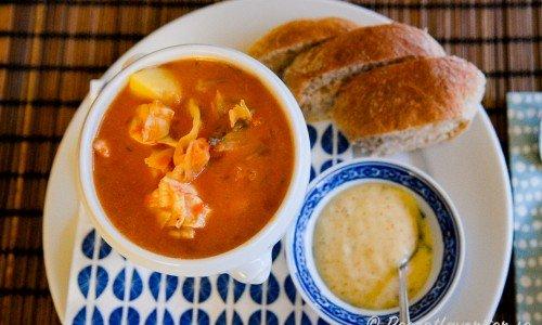 Fisksoppa med torsk och potatis i soppskål serverad med aioli och bröd