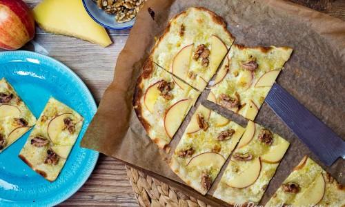 Nybakt Flammkuchen eller Tarte flambée med ost, äpple och valnötter