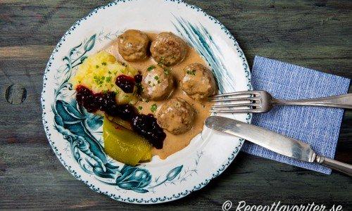 Fläskfärsbullar med gräddsås, potatismos, saltgurka, lingon och hackad persilja.
