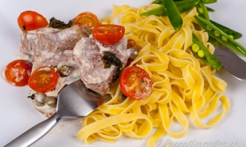 Fläskfilé med gorgonzola, grädde, tomater och kapris serverad med pasta tagliatelle